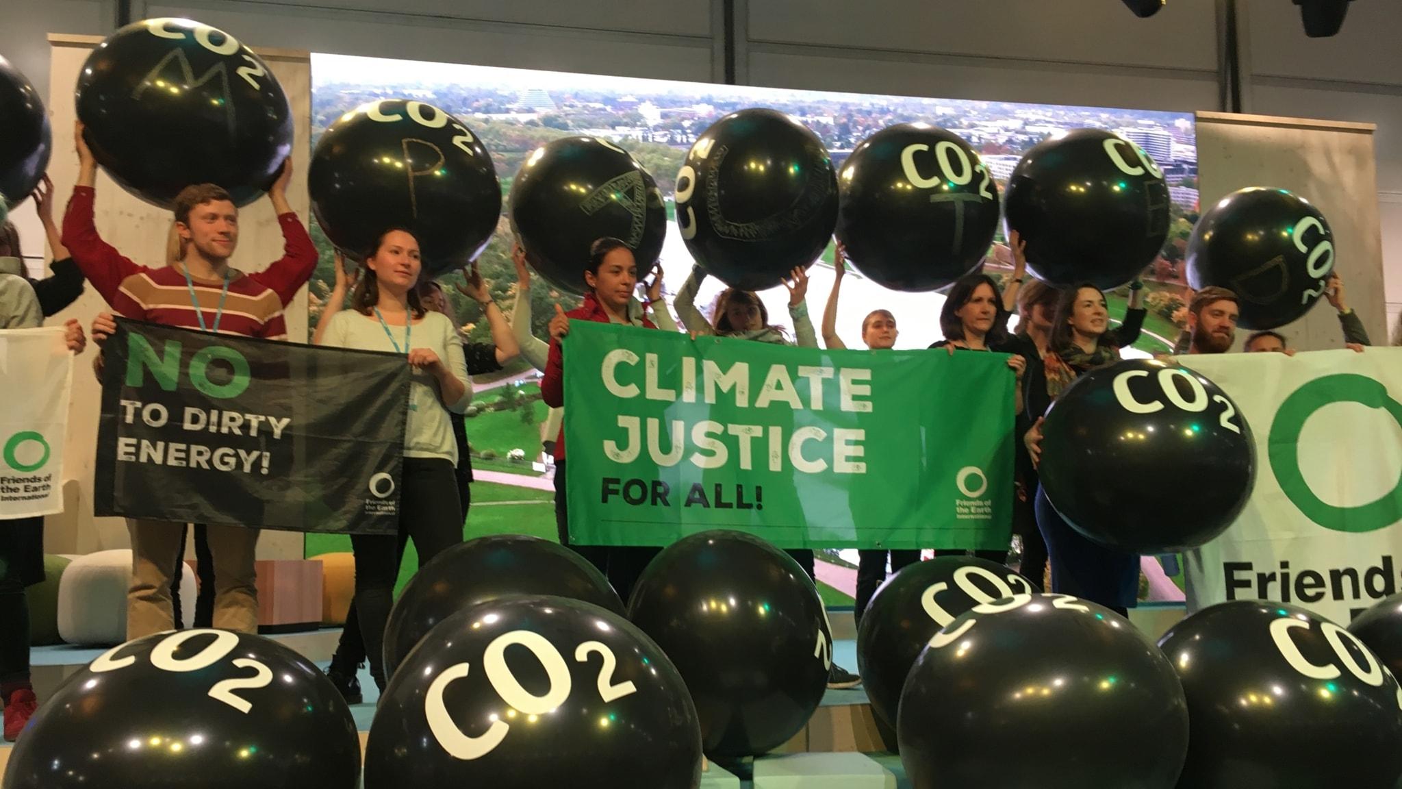 Ungdomar håller upp svarta ballonger med texten CO2 och visar banderoller med texten No to dirty energy och Climate justice for all