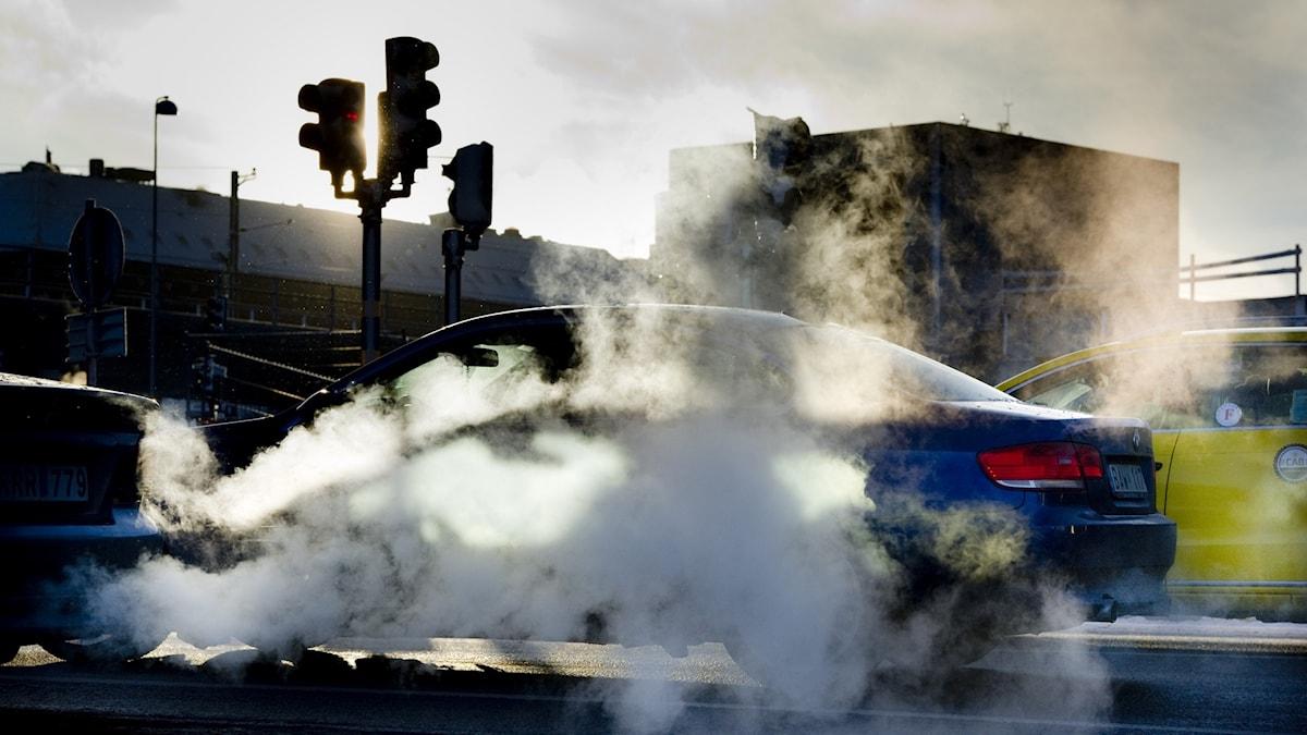Bilar och stora moln av avgaser.