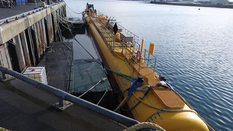 En ubåtsliknande, 64 meter lång tub. Den ligger i hamnkajen och guppar upp och ner i vattnet.