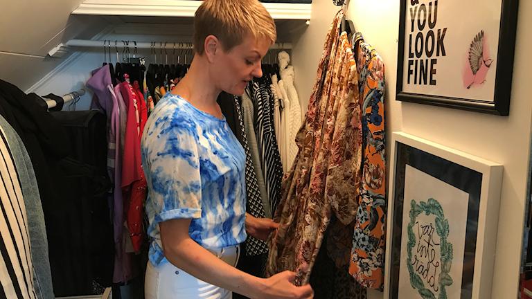 En kvinna står i en garderob full av kläder.