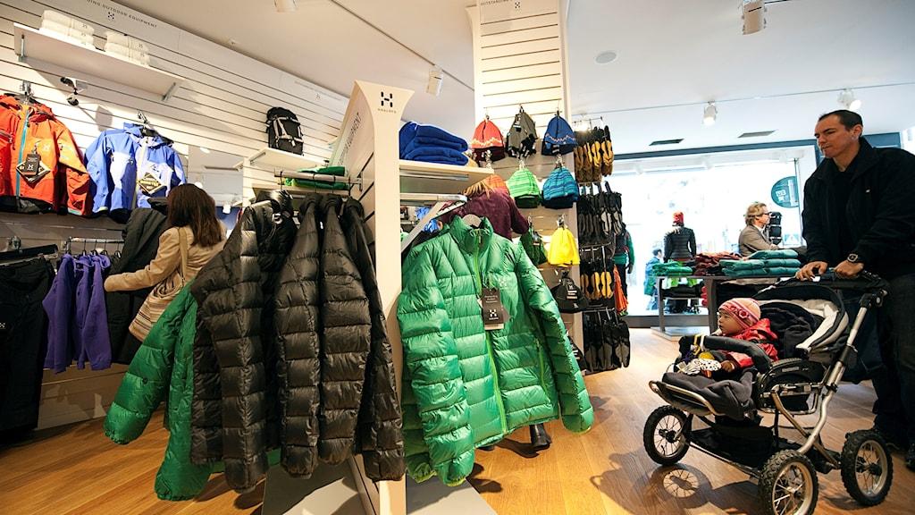gröna och svarta dunjackor hänger på galgar i en affär.