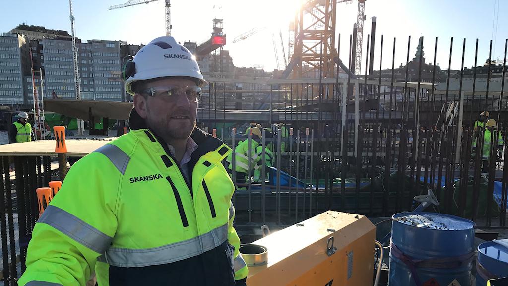 En byggjobbare i gul jacka på en byggarbetsplats