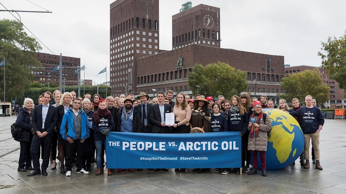 En grupp människor står framför rådhuset i Oslo och håller i en banderoll med texten the people vs Arctic oil
