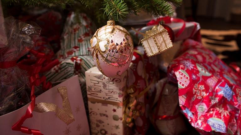 Julklappar under gran med snören och en glittrande guldkula som hänger ner.