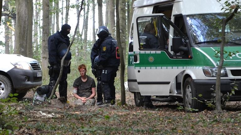 En ung man på knä mellan två uniformerade poliser