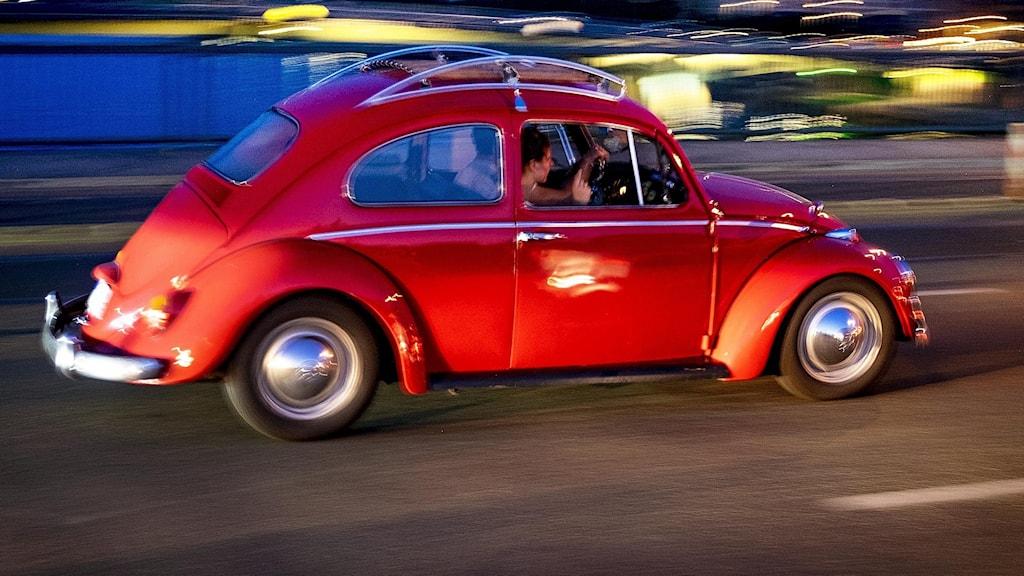 Röd Volkswagen bubbla kör mot blå bakgrund