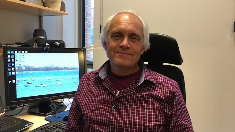 Man med grått hår och rödrutig skjorta sittande vid skrivbord med