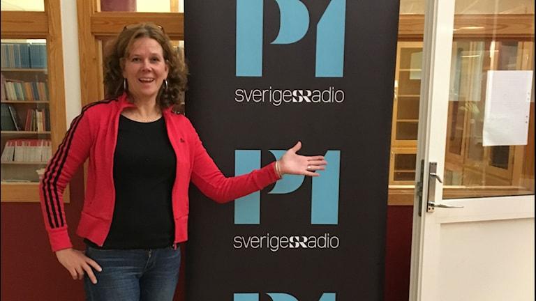 kvinna i klarröd adidasjacka framför P1 skärm