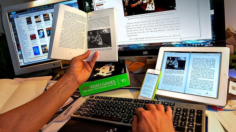 Bild på skrivbord med tangentbord och en massa dataskärmar, läsplattor, böcker mm