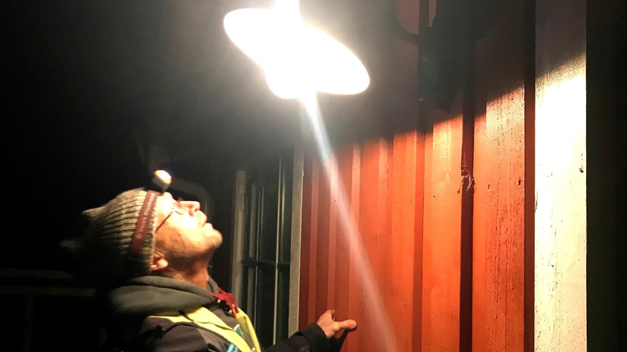 Ekologen Jan Olof Helldin, från Sveriges Lantbruksuniversitet, undersöker en utomhuslampa vid en sommarstuga i Södermanland.