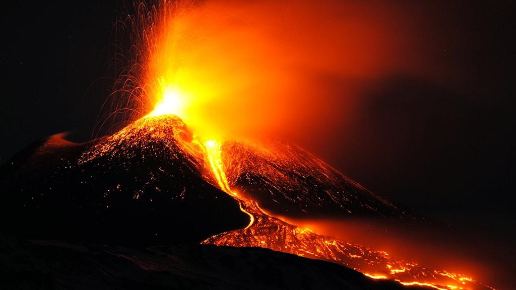 Svart vulkan sprutar ut orange lava