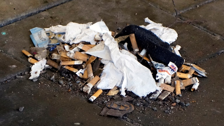 En hög med cigarettfimpar och skräp ligger på marken