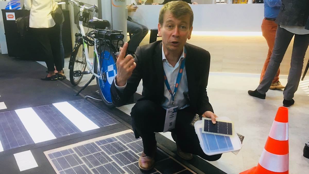 En man sitter på huk på en ett golv med plattor av solceller.