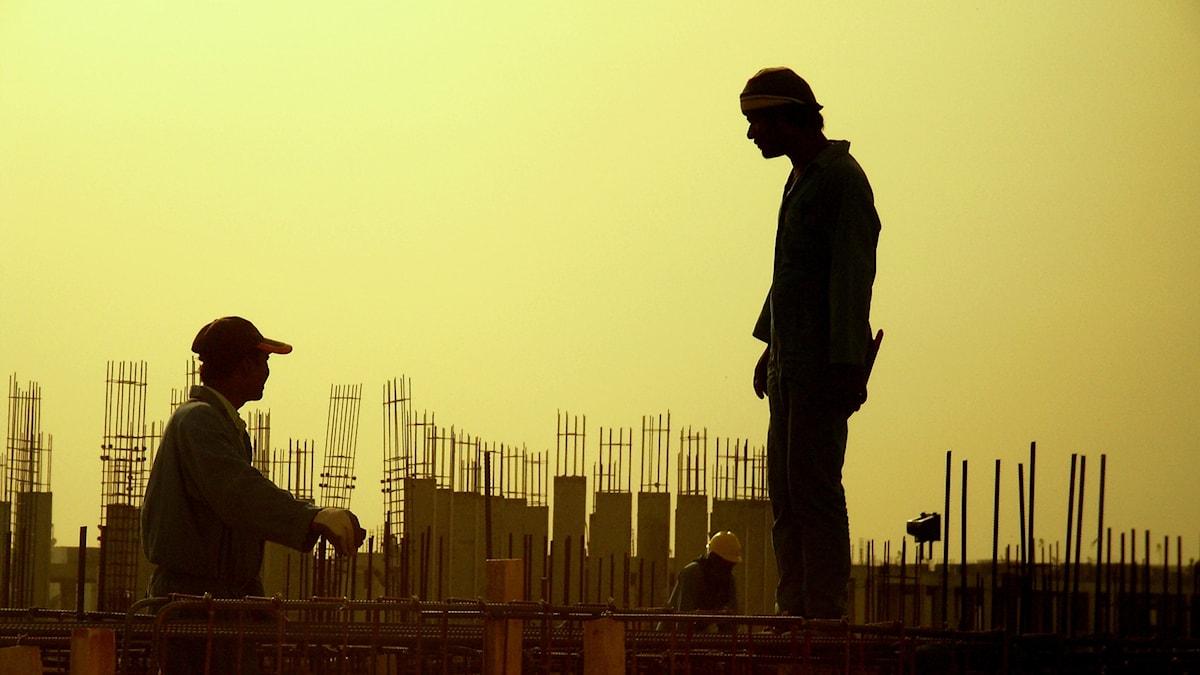 Silhuetten av två män som står på en byggnadsställning mot en gul himmel.