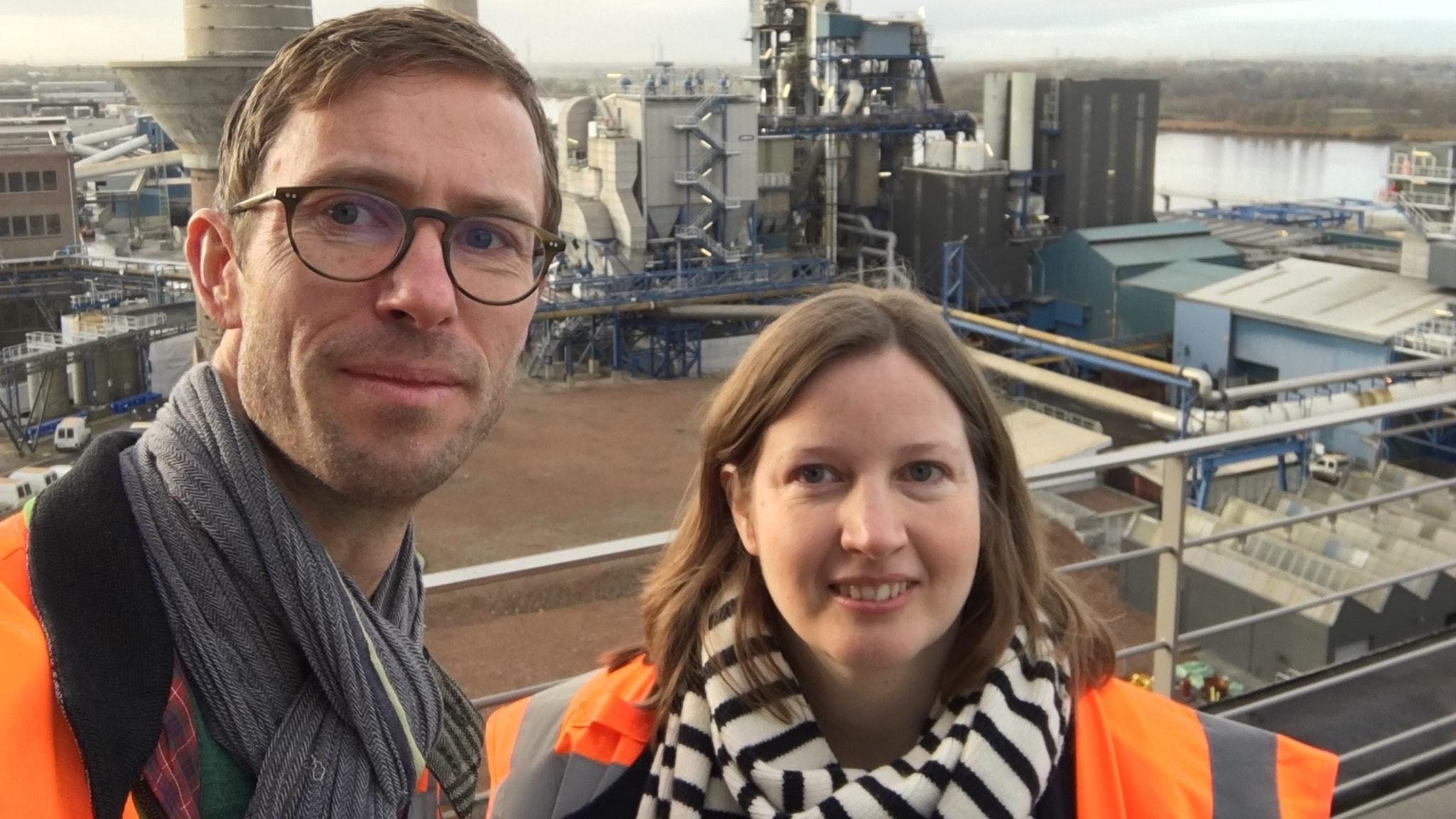 En man och en kvinna står framför en fabrik som återvinner laddbara batterier