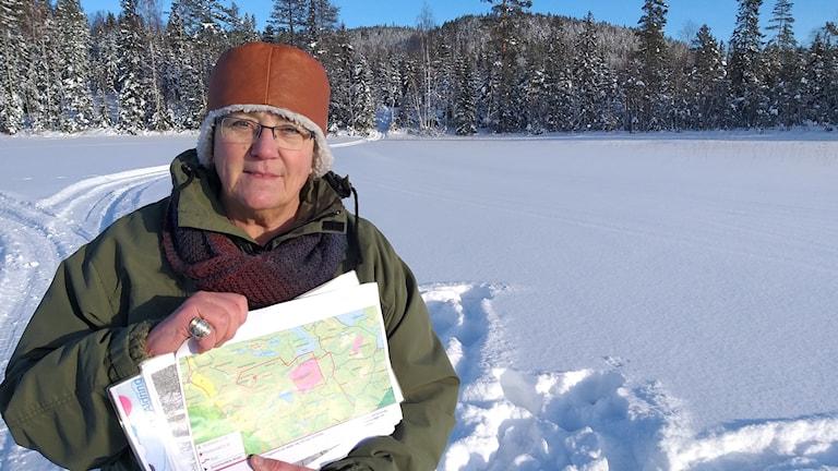 En kvinna står ute på en snöklädd is och håller i en karta