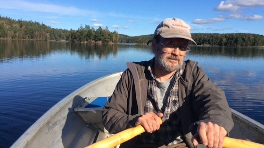En man ror på en stilla sjö. Himlen är blå.