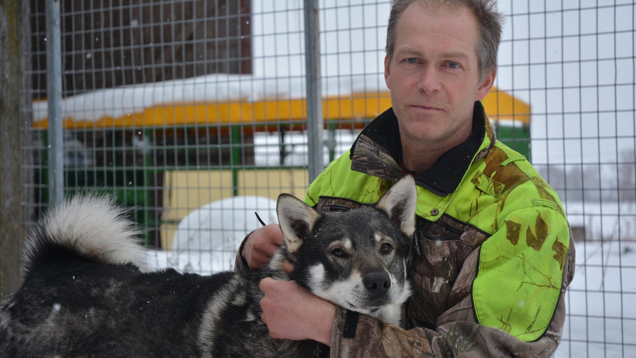 En man håller om sin gråa hund