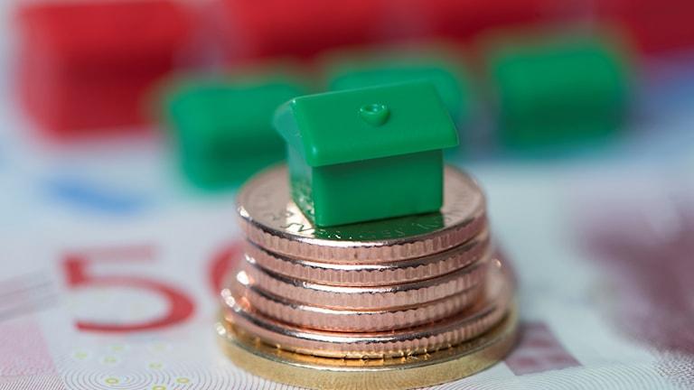 Svenska mynt ligger i en stapel på en femhundrakronorssedel och med ett grön monopolhus på toppen.