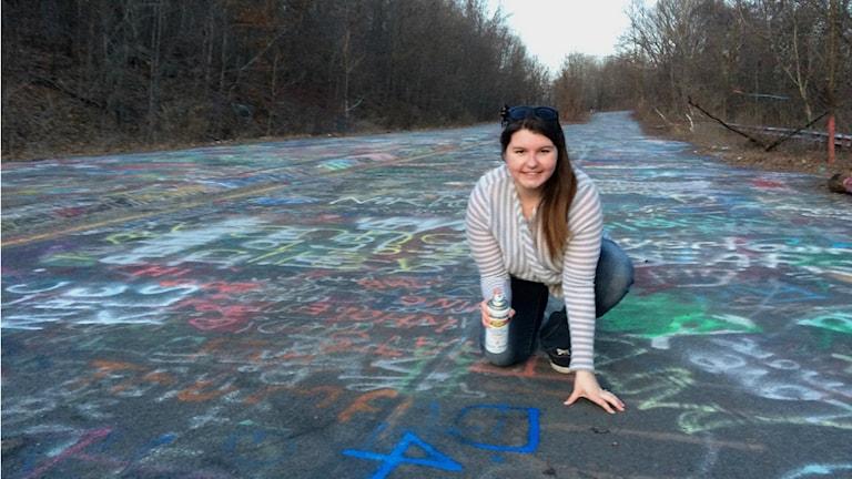 Devin sprayar sin pojkväns namn på Graffiti highway i Centralia.
