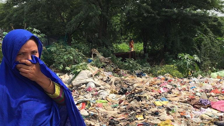 En indisk kvinna står framför en plats där byborna går för att kissa och bajsa i brist på toaletter. Hon håller sin blåa sjal för näsan
