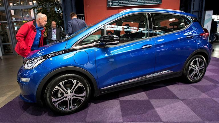 Man i röd jacka står till vänster i bild och tittar på en glänsande, blå elbil