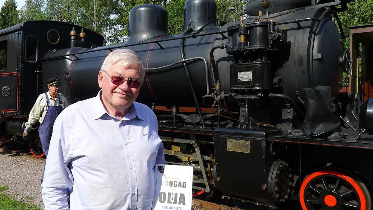Professor Kjell Aleklett visar sin nya bok vid ett koleldat ånglok utanför Uppsala.