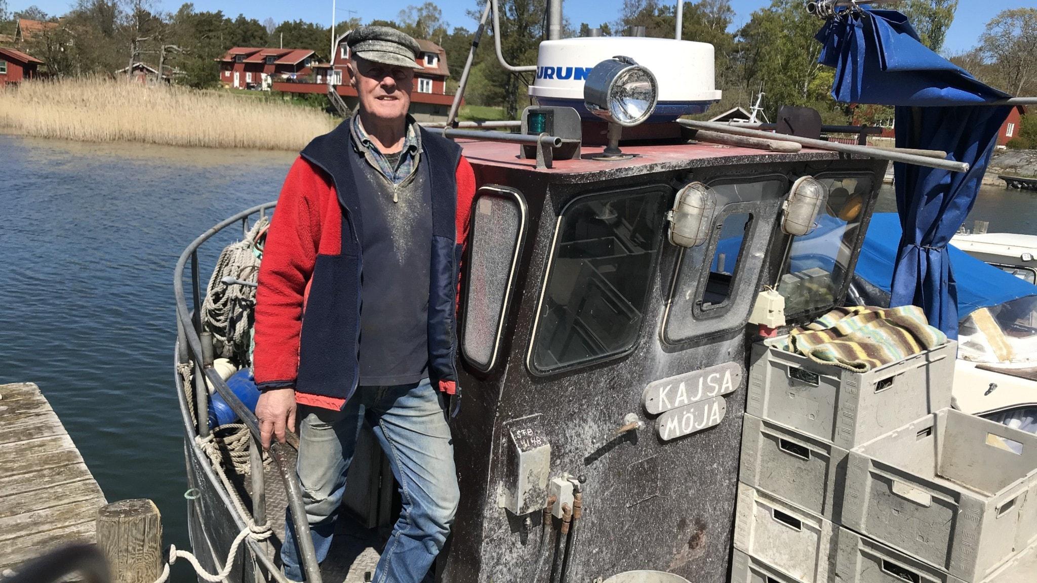 En fiskare står i sin båt som är anlagd vid en brygga.