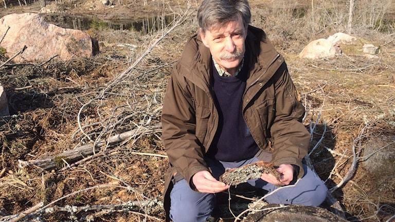En man sitter på ett skogshygge och håller en bit bark i handen
