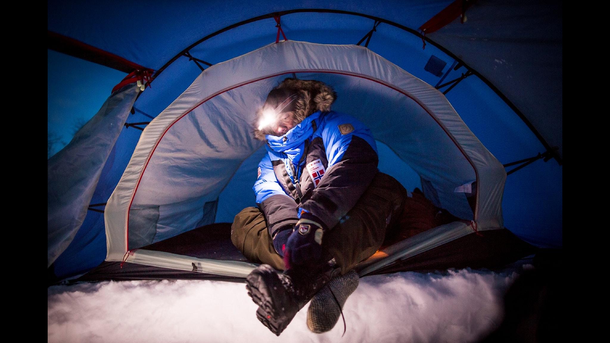 man som sitter i tält med tjocka vinterkläder på sig