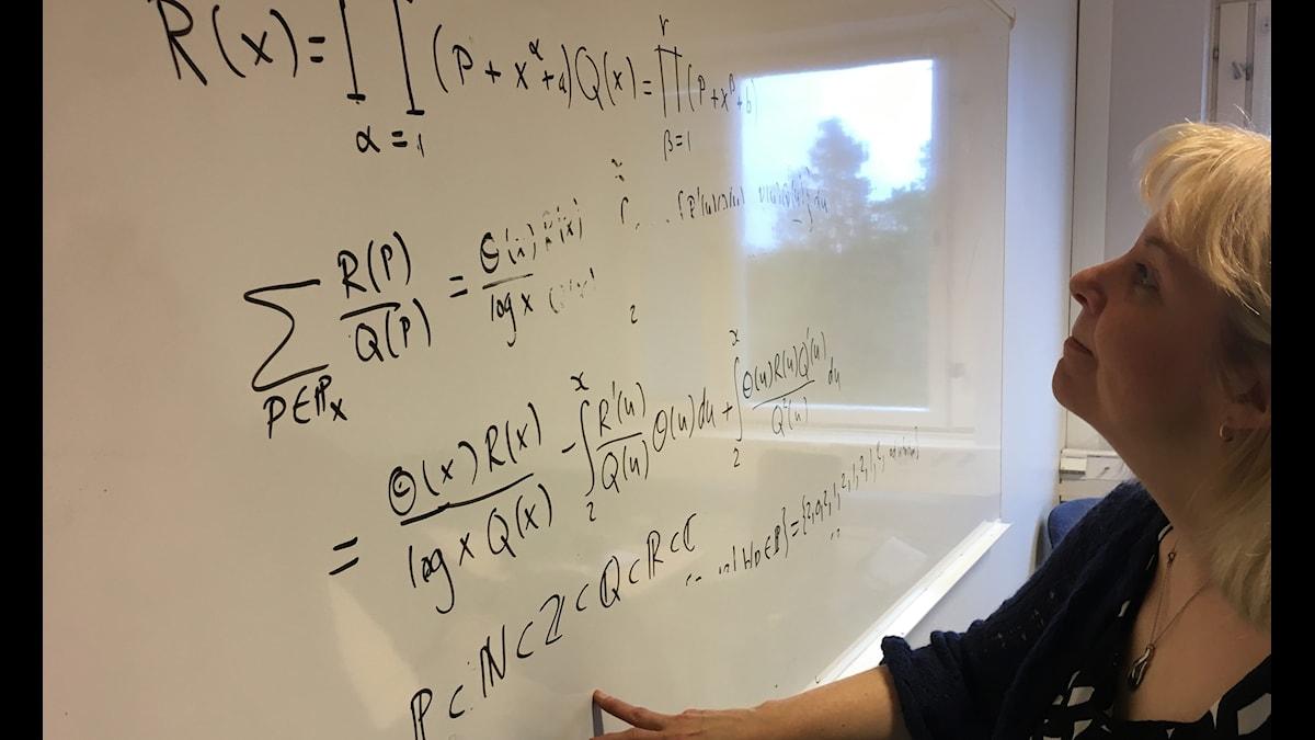Anna Wedestig tittar på en tavla med mattematiska uträkningar.