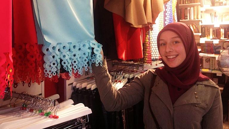 Amra Masic, som burit hijab sedan hon var tolv, visar upp sjalar i en av Sveriges största butiker för muslimska varor. Foto: Natacha Lopez/SR