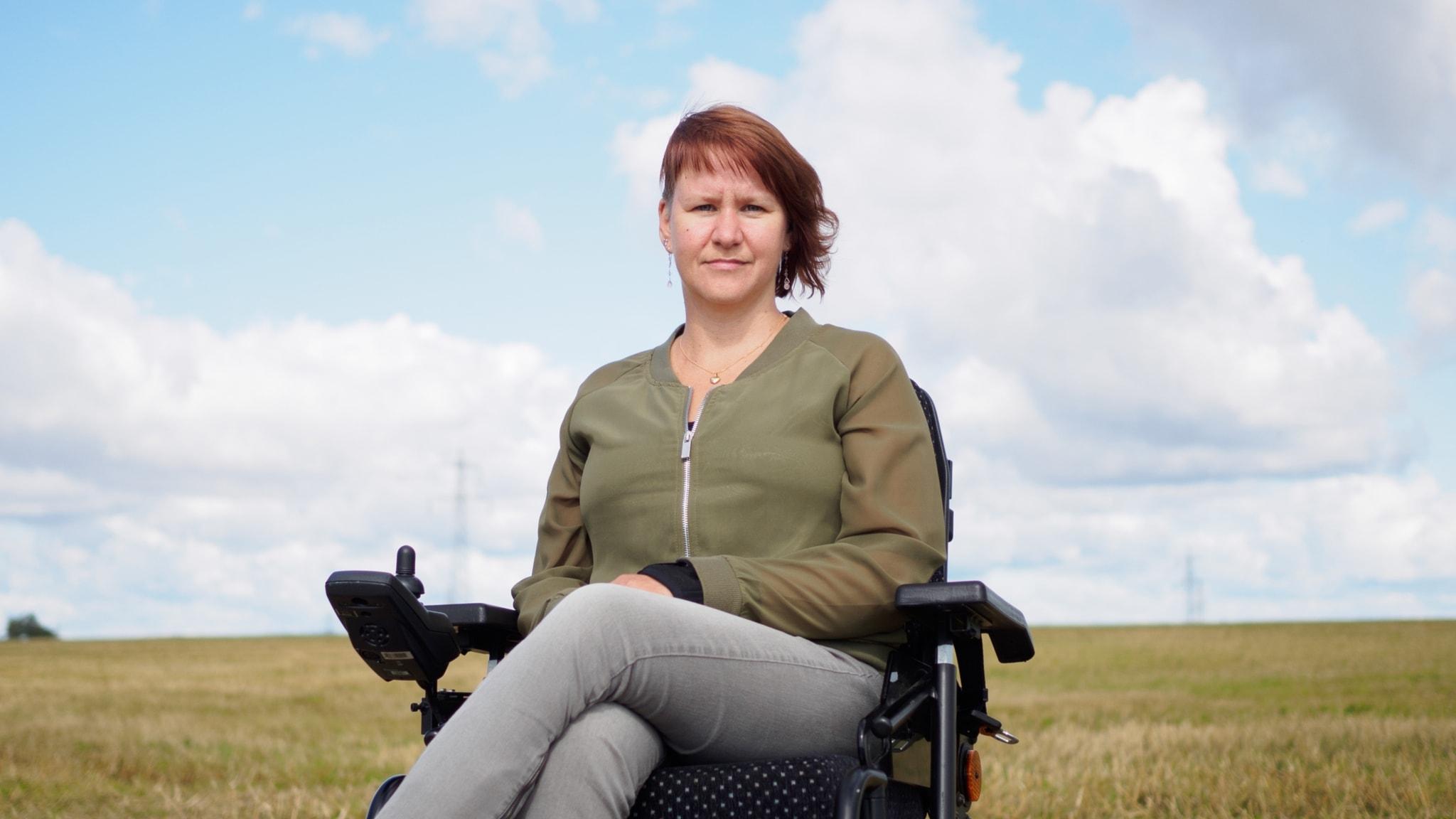 Madelen Löw startade startade organisationen We Rise Again för att stötta andra med funktionsnedsättning som utsatts för övergrepp. Madelen i sin permobil framför ett sädesfält med blå himmel och moln i bakgrunden.