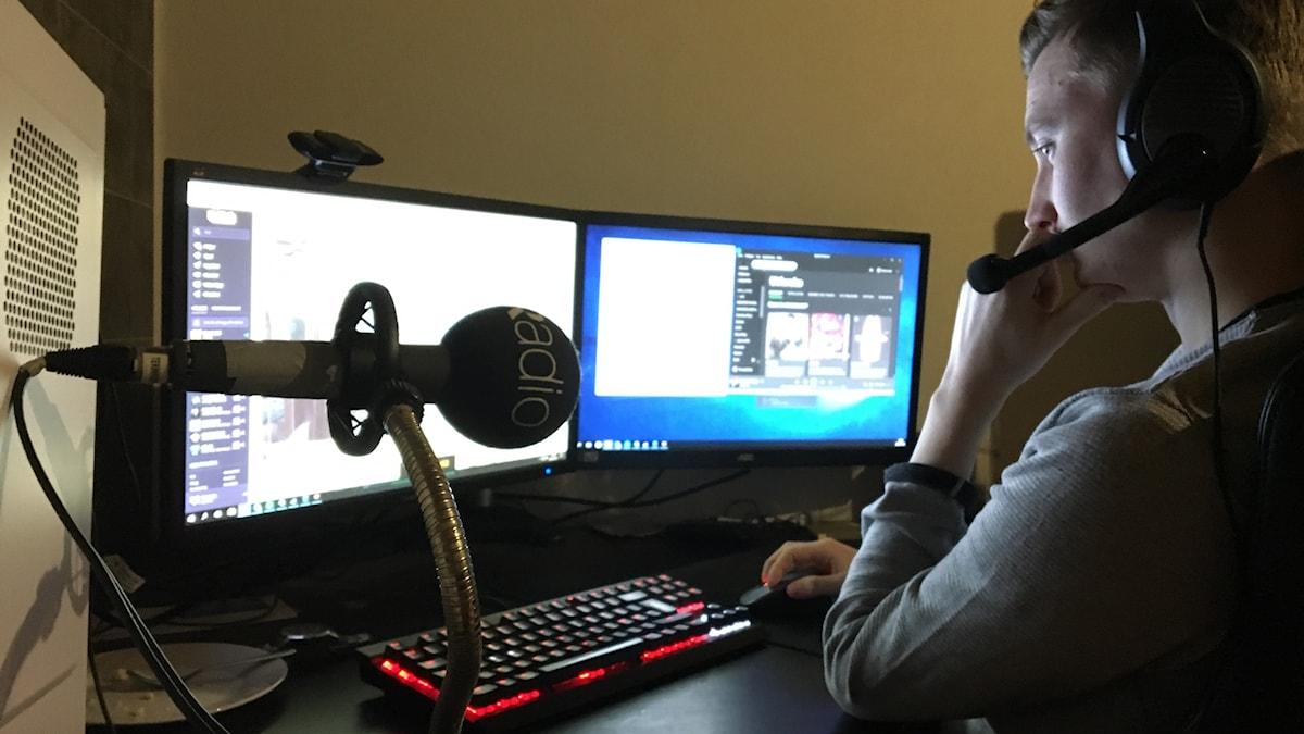 Andre Brännvall sitter framför sin dator med dubbla skärmar och spelar Smite.