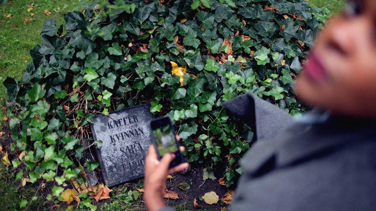Gravsten och kvinna med mobil i handen
