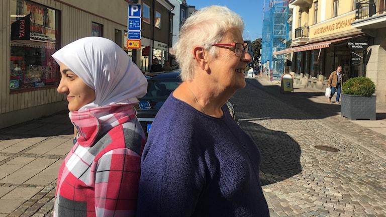 Hazar Samra och Britt-Mari Bohman står med ryggarna mot varandra på en gata.