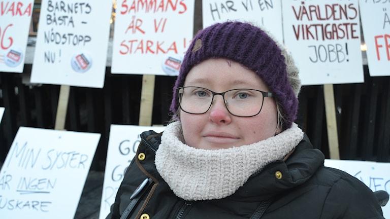 Elin framför plakaten på demonstrationen i Umeå mot indragna assistensbeslut