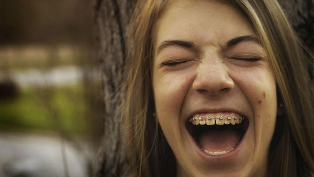 Tjej i tandställning som skrattar