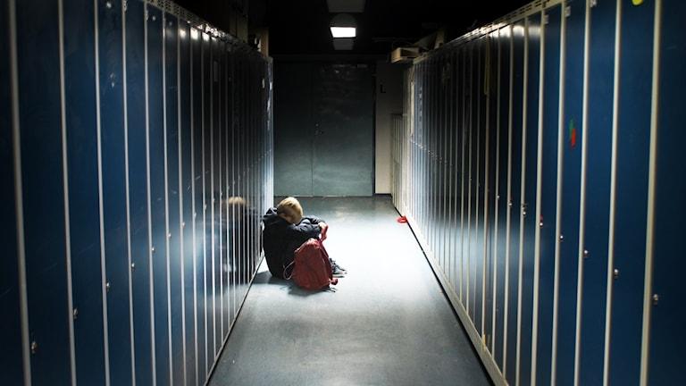 Pojke sitter i ljuset mellan rader av plåtskåp.
