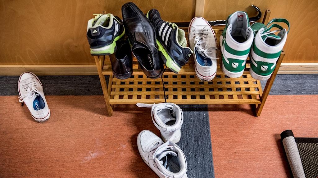 Flera par skor trängs på en liten skohylla.
