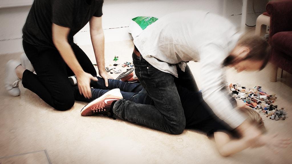 En man håller fast benen medan en annan håller fast armarna på en pojke liggandes på mage.