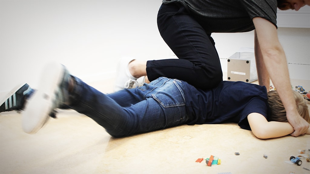 En man sätter ett knä i ryggen på en pojke liggandes på mage, och håller ner pojkens händer mot golvet.