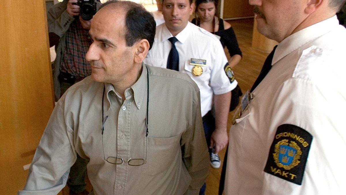 Amir Heidari omgärdad av väktare. Foto: Adam Ihse/TT.