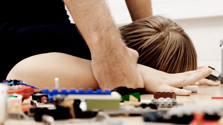 En vuxen mans händer håller ner ett barns händer mot golvet. På golvet ligger legobitar utspridda.