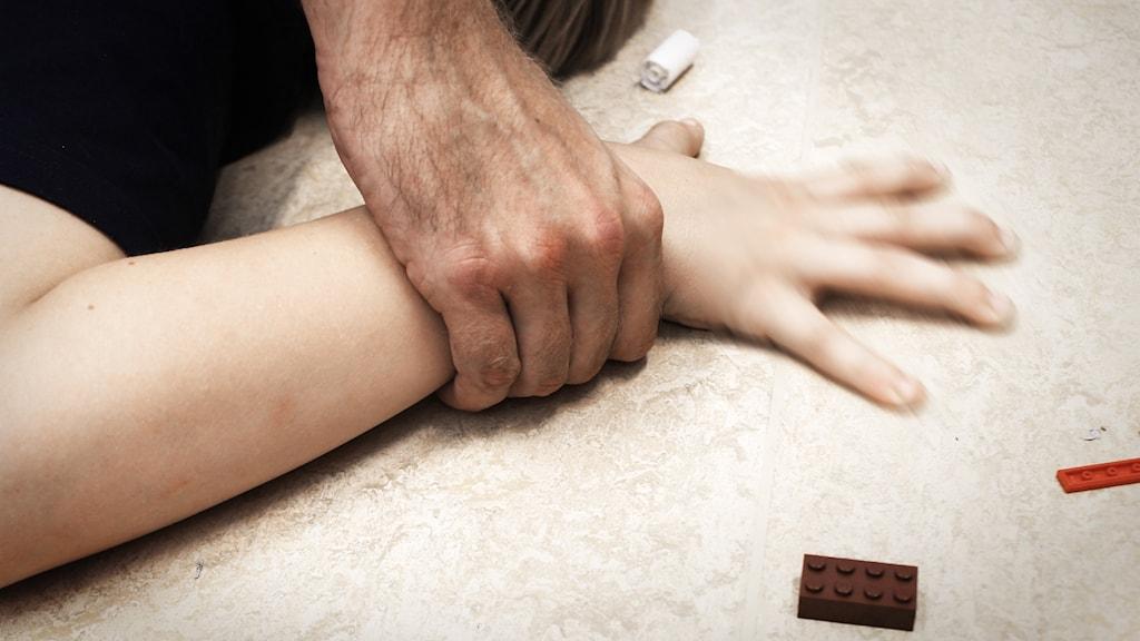 En vuxen mans hand håller ner ett barns hand mot golvet.