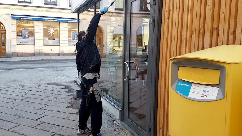 Man sedd från sidan, tvättar skyltfönster.
