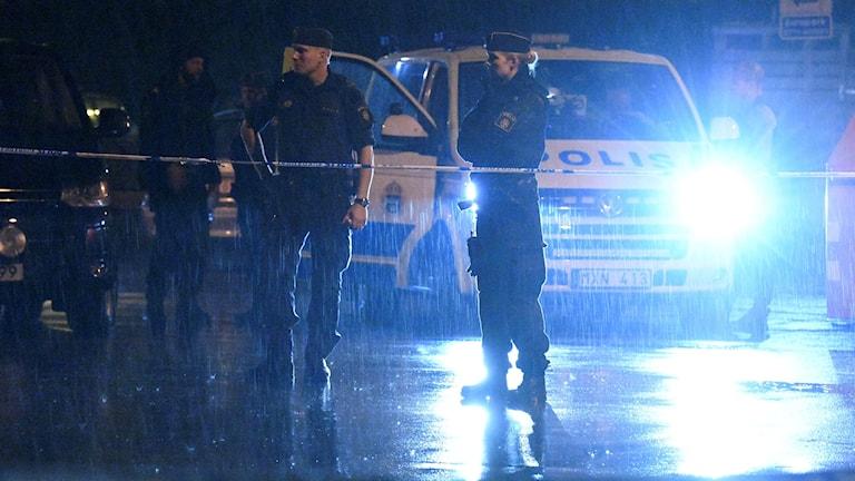 Poliser håller avspärrning nattetid på regnig väg.