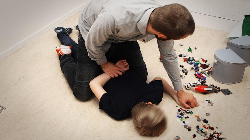 En man gränslar ett barn på ett golv med utspridda legobitar.