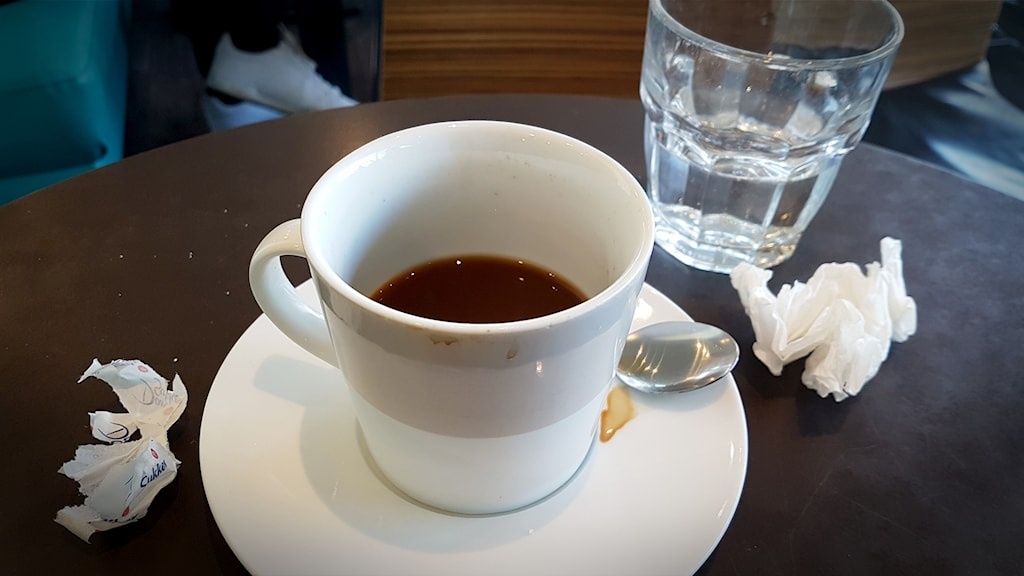 Kaffekopp med fläckar, omslagspapper från sockerbit.