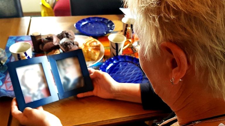 Anne Charlotte tittar på fotografier i en ram.